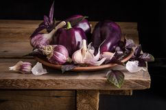 Dark purple peppers with leaves of basil and garlic on old rustic wooden table royalty free stock image