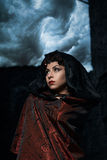 Dark queen of the ghost in a dark castle collapsed, visible destruction of the castle wall and dark storm clouds. In the sky Royalty Free Stock Images