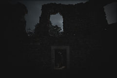Dark queen of the ghost in the dark ruined castle glows in the dark night. Visible walls of the ruined castle Royalty Free Stock Photo