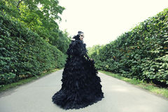 Dark Queen in park. Fantasy black dress Stock Image