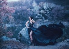 The dark queen pose against the background of gloomy rocks. A luxurious black dress with a long train fluttering in the royalty free stock photos