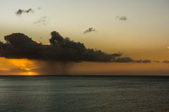 Dark rain cloud and rain at sunrise over the Atlantic Stock Photo