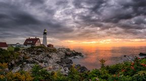 Dark rain clouds and a rising sun at Portland Head Lighthouse royalty free stock photography