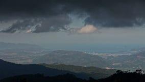 Dark Rainy Cloud Motion above Hills Resort City Ocean. Dramatic rainy dark grey cloud motion in blue sky above hills resort city and ocean getting dark stock video footage