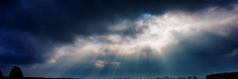 Dark rainy sky and bright sun rays against the background of clouds. Web banner for your design royalty free stock images