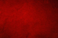 Dark red background. Fabric with soft folds and smudges in uneven candlelight Royalty Free Stock Photo