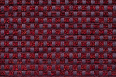 Dark red background from checkered pattern textile, closeup. Structure of the wicker fabric macro. Royalty Free Stock Images