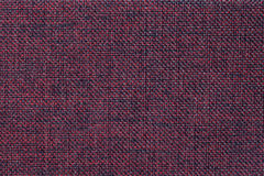 Dark red background of dense woven bagging fabric, closeup. Structure of the textile macro. Royalty Free Stock Image