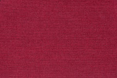 Dark red background from a textile material with wicker pattern, closeup. Structure of the wine fabric with natural texture. Cloth backdrop Stock Photos