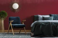 Dark red bedroom interior. Wooden armchair next to bed in dark red bedroom interior with plant and gold mirror royalty free stock photo