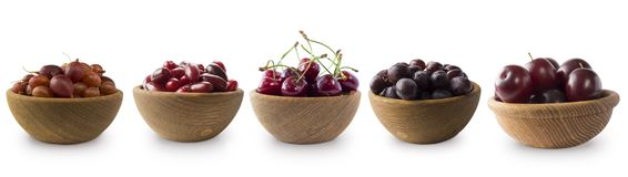 Dark red berries on a white background. Cherries, gooseberries, grapes and plums in a wooden bowl. Berry with copy space for text. Ripe and tasty berries Royalty Free Stock Photo