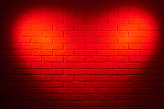 Dark red brick wall with heart shape light effect and shadow, abstract background photo Royalty Free Stock Images