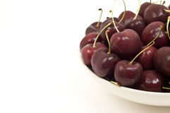 Dark red cherries. Dark red Bing or Lapin cherries isolated on white background in horizontal format with copyspace Stock Images