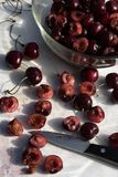 Dark red cherries cut into halves on white cutting board. Dark red cherries halved on white cutting board and in clear glass bowl in food preparation kitchen royalty free stock photos