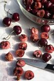 Dark red cherries cut into halves on white cutting board. Dark red cherries halved on white cutting board and in clear glass bowl in food preparation kitchen stock photos