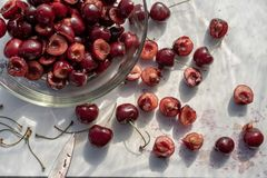 Dark red cherries cut into halves on white cutting board. Dark red cherries halved on white cutting board and in clear glass bowl in food preparation kitchen stock photography