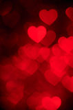 Dark red color heart bokeh background photo. Abstract holiday, celebration backdrop. Stock Photos
