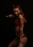 Dark red devil girl with a kni Stock Images