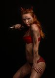 Dark red devil girl with a knife Royalty Free Stock Images