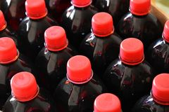 Dark red fruit syrup in plastic bottles royalty free stock photography