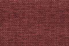 Dark red knitted woolen background with a pattern of soft, fleecy cloth. Texture of textile closeup. Royalty Free Stock Photo