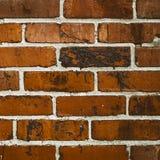 Dark red orange brick wall square. Dark red orange brick wall horizontal pattern abstract background. Dark grungy orderly bricks splotch of dirty black tar royalty free stock photos