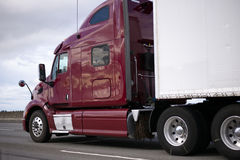 Dark red professional big rig semi truck with trailer on the roa Royalty Free Stock Image