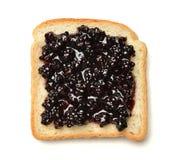 Dark red raspberry preserves spread over a slice of white sandwich Stock Image