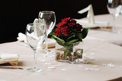 Dark red rose arrangement on dinner table Stock Image