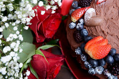 Dark Red Roses and Chocolate Cake with Berries Royalty Free Stock Photos