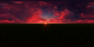 Dark red sunset in a grass field. This picture represents a blue sky with dark red clouds in a grass field Stock Images