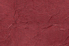 Dark red wavy background from a textile material. Fabric with fold texture closeup. Stock Image