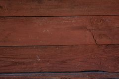 Dark red wooden faded planking background with cracks. And splits on it stock images