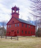 Spooky old haunted church2. Dark red wooden New England church building on a dark day with square tower and multi paned windows, nine over nine, surrounded by Royalty Free Stock Photography