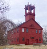 Spooky old haunted church. Dark red wooden New England church building on a dark day with square tower and multi paned windows, nine over nine, surrounded by Stock Photography
