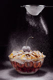 Dark refined breakfast with cherry and flow falling powdered sugar. Royalty Free Stock Images