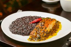 Dark risotto with grilled salmon stock photography