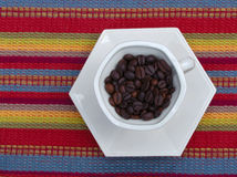 Dark roast coffee beans in cup Stock Image