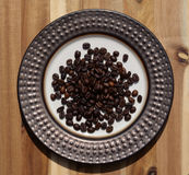 Dark roast coffee beans on decorative plate Stock Image