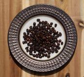 Dark roast coffee beans on decorative plate Stock Image