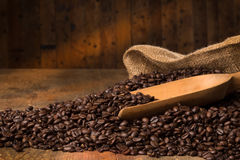 Dark roasted beans on a wooden table. Some roasted beans on a wooden table with a serving spoon Stock Photos