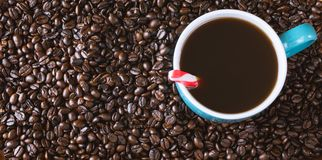 Dark roasted coffee beans background with blue filled coffee cup with peppermint Stock Photo
