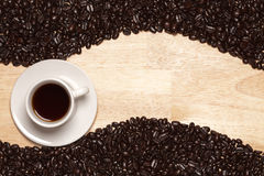 Dark Roasted Coffee Beans & Cup on Wood Background Stock Photography