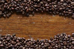 Dark roasted coffee beans framing wooden area Stock Images