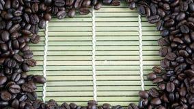 Dark roasted coffee beans. Put on bamboo Stock Image