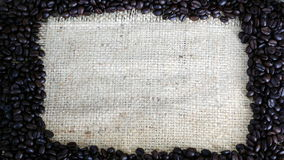 Dark roasted coffee beans. Put on a sack Royalty Free Stock Photo