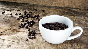 Dark roasted coffee beans. Put on a wood table Royalty Free Stock Images
