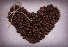 Dark roasted coffee beans  in the shape of a heart with a bow on Stock Photography