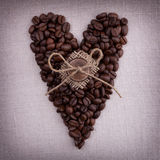 Dark roasted coffee beans  in the shape of a heart with wooden b Stock Image