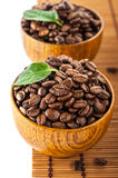 Dark roasted coffee beans in wooden bowl Stock Photo